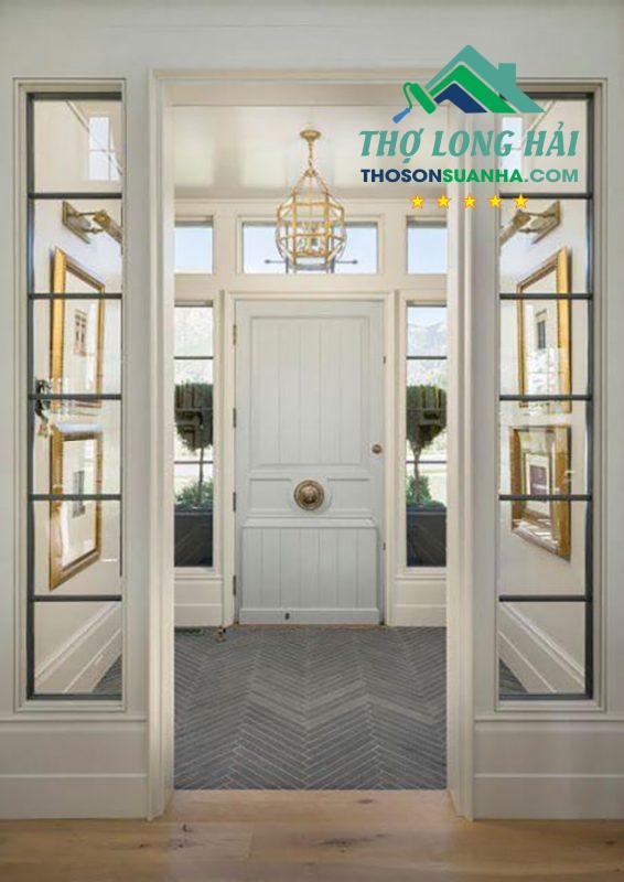 Cánh cửa gỗ chính với màu tráng xám tinh tế và nền nã giúp mang đến một vẻ đẹp hiện đại và trẻ trung
